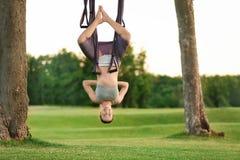 Jonge vrouw die luchtyoga op boom uitoefenen Stock Foto's