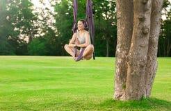 Jonge vrouw die luchtyoga op boom uitoefenen Royalty-vrije Stock Afbeeldingen