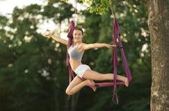 Jonge vrouw die luchtyoga op boom uitoefenen Stock Afbeelding