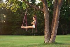 Jonge vrouw die luchtyoga op boom uitoefenen Stock Foto