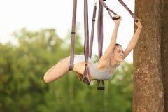 Jonge vrouw die luchtyoga op boom uitoefenen Royalty-vrije Stock Fotografie