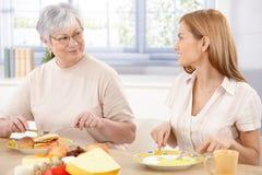 Jonge vrouw die lunch met moeder het glimlachen heeft Royalty-vrije Stock Afbeeldingen