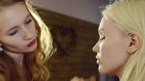 Jonge vrouw die make-up op een model in een schoonheidssalon doen stock videobeelden