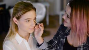 Jonge vrouw die make-up toepassen om in salon te modelleren stock videobeelden