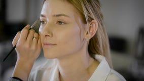 Jonge vrouw die make-up toepassen om in salon te modelleren stock video