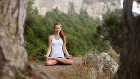 Jonge vrouw die, meisje die yogahoogte in de bergen doen, het concept van de ontspannings zelf-bezinning in openlucht mediteren Stock Fotografie
