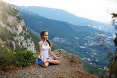 Jonge vrouw die, meisje die yogahoogte in de bergen doen, het concept van de ontspannings zelf-bezinning in openlucht mediteren Stock Afbeeldingen