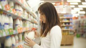 Jonge vrouw die melk in kruidenierswinkelopslag kiezen stock video