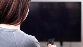 Jonge vrouw die met afstandsbediening op slimme TV letten stock footage