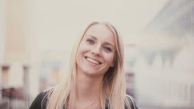 Jonge vrouw die met blonde lang haar camera en het glimlachen bekijken Portret van aantrekkelijk meisje op de achtergrond van het stock videobeelden