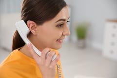Jonge vrouw die met gehoorapparaat op telefoon binnen spreken stock fotografie