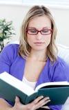 Jonge vrouw die met glazen een boek leest Royalty-vrije Stock Afbeeldingen