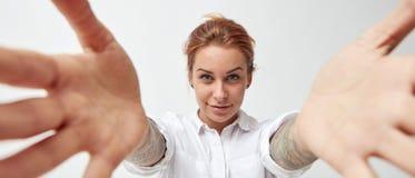 Jonge vrouw die met haar wapens open op witte achtergrond glimlachen royalty-vrije stock foto
