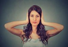 Jonge vrouw die met handen haar gesloten oren behandelen Hoor geen kwaad concept Stock Foto