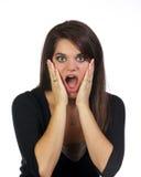 Jonge vrouw die met handen haar gezicht verrast houdt Royalty-vrije Stock Foto