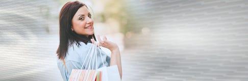Jonge vrouw die met het winkelen in hand zakken, lichteffect lopen Panoramische banner royalty-vrije stock foto's