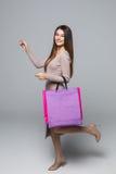 Jonge vrouw die met het winkelen zak en gerichte hand lopen die over grijze achtergrond wordt geïsoleerd Stock Afbeeldingen