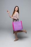 Jonge vrouw die met het winkelen zak en gerichte hand lopen die over grijze achtergrond wordt geïsoleerd Royalty-vrije Stock Foto