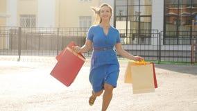 Jonge vrouw die met het winkelen zakken in handen in openlucht lopen stock videobeelden