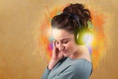 Jonge vrouw die met hoofdtelefoons aan muziek luisteren stock foto