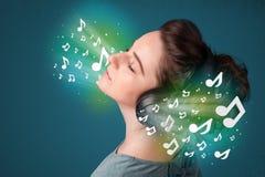 Jonge vrouw die met hoofdtelefoons aan muziek luisteren royalty-vrije stock afbeelding