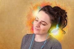 Jonge vrouw die met hoofdtelefoons aan muziek luisteren Stock Afbeelding