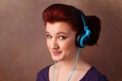 Jonge vrouw die met hoofdtelefoons aan muziek met exemplaarruimte luisteren Royalty-vrije Stock Fotografie