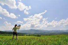Jonge vrouw die met kaart een enorme wildernis onderzoekt Royalty-vrije Stock Foto's