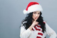 Jonge vrouw die met Kerstmanhoed een stil gebaar maken stock afbeeldingen