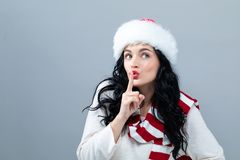 Jonge vrouw die met Kerstmanhoed een stil gebaar maken stock foto