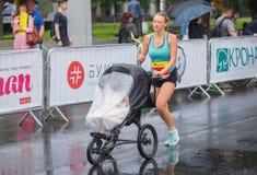 Jonge vrouw die met kinderwagen lopen tijdens van het Halve de Marathon` ras van ` Interipe Dnipro royalty-vrije stock afbeelding