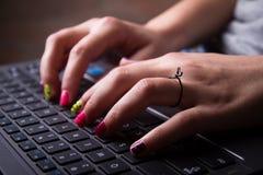 Jonge vrouw die met kleurrijke spijkers op laptop toetsenbord typen Stock Afbeeldingen