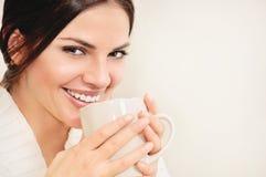 Jonge vrouw die met lang haar en bruine ogen koffie of thee drinken Royalty-vrije Stock Afbeeldingen