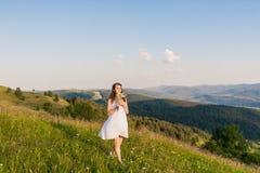 Jonge vrouw die met lang haar op een berglandschap kijken stock foto's