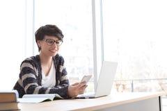 Jonge vrouw die met mobiele telefoon werken stock foto's
