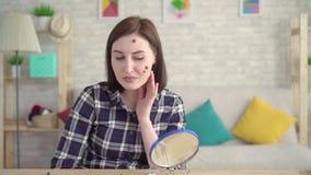 Jonge vrouw die met mollen op haar gezicht in de spiegel kijken stock video