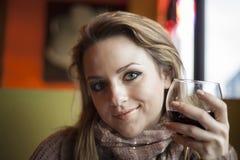 Jonge Vrouw die met Mooie Blauwe Ogen Rode Wijn drinken stock foto's