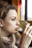 Jonge Vrouw die met Mooie Blauwe Ogen Rode Wijn drinken stock afbeelding