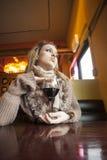 Jonge Vrouw die met Mooie Blauwe Ogen Rode Wijn drinkt stock afbeelding
