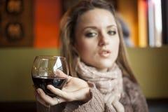 Jonge Vrouw die met Mooie Blauwe Ogen Rode Wijn drinkt stock foto's