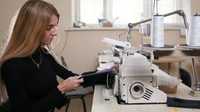 Jonge vrouw die met naaimachine aan fabriek werken stock videobeelden