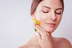 Jonge vrouw die met natuurlijke make-up een bloem houden Organisch schoonheidsmiddelenconcept stock foto's