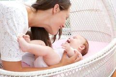 Jonge vrouw die met pasgeboren zuigeling glimlachen Royalty-vrije Stock Afbeeldingen