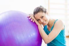 Jonge vrouw die met physioball bij gymnastiek uitoefenen Stock Afbeeldingen