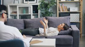 Jonge vrouw die met psycholoog het liggen op bank in bureau het spreken het gesturing spreken stock videobeelden