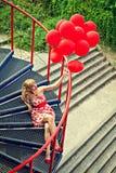 Jonge vrouw die met rode ballons op de stappen zitten royalty-vrije stock afbeelding