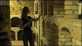 Jonge vrouw die met rode wijnglas fles in kelder kijken Vrouwen winemaker proevende rode wijn in traditionele kelder stock footage