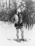 Jonge vrouw die met sneeuwschoenen door het hout lopen (Alle afgeschilderde personen leven niet langer en geen landgoed bestaat l Stock Afbeeldingen