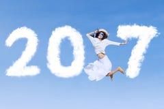 Jonge vrouw die met 2017 springen Stock Foto's