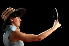 Jonge vrouw die met strohoed op spiegel kijkt stock afbeeldingen